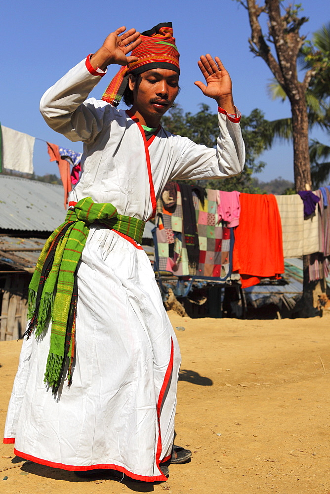 A Tripura tribesman performing a traditional dance wearing white robes, in their village in the Bandarban region of Bangladesh, Asia *** Local Caption *** black and white levels adjusted  - 826-590
