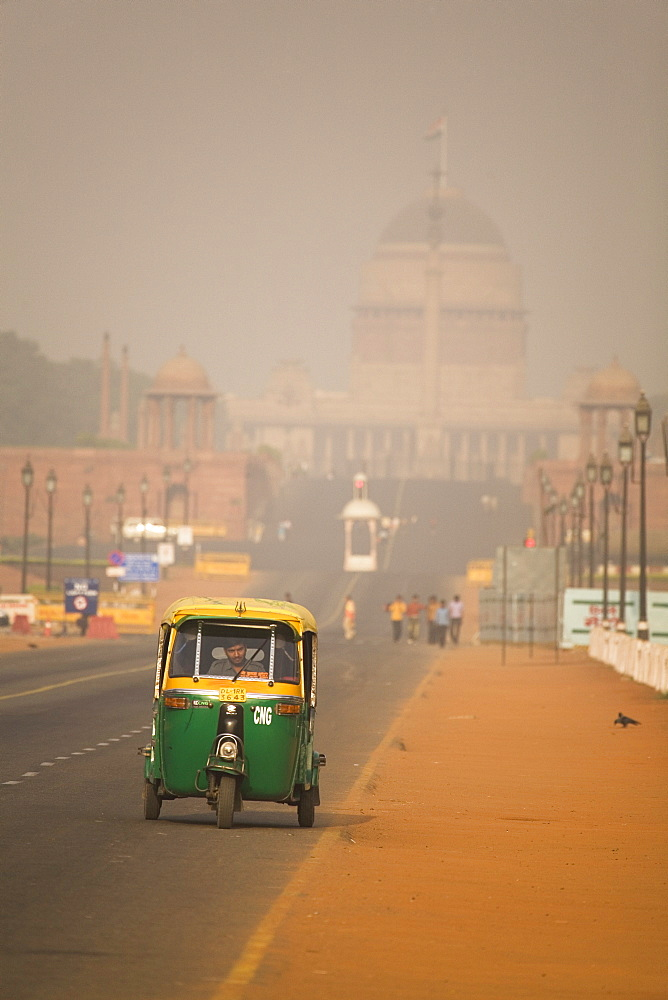 An auto rickshaw drives along the Rajpath, in front of the Rashtrapati Bhavan (President's Palace), on a hazy day in New Delhi, India, Asia