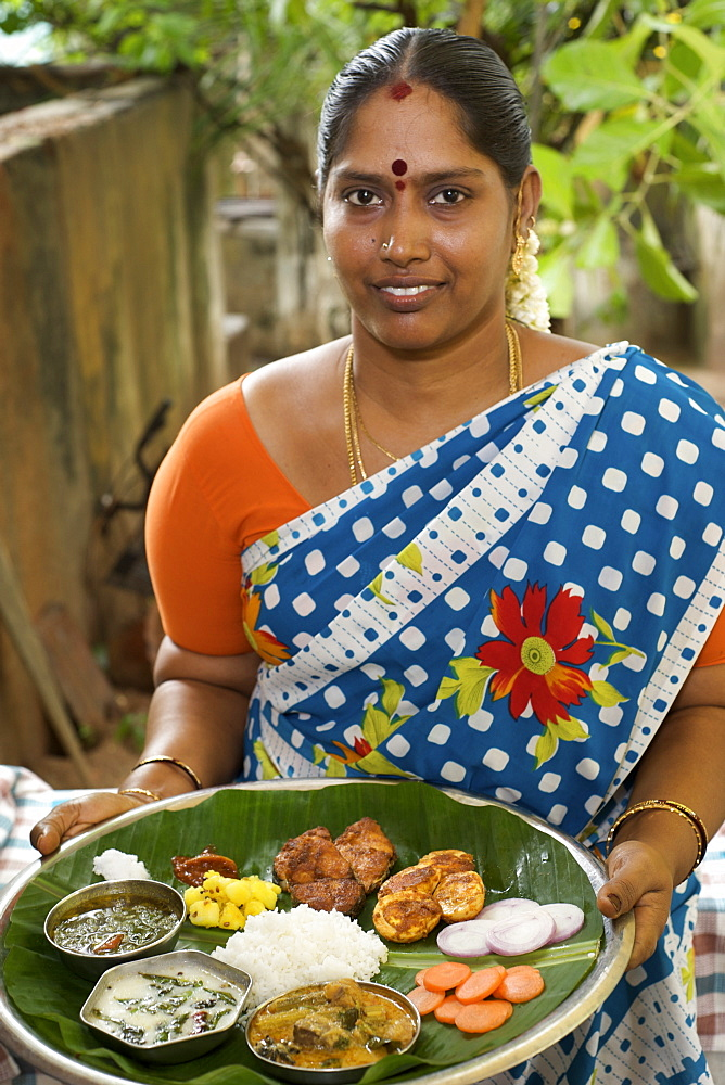Mrs Vijayalakshmi Neelakandan with complete meal in a thali covered with a banana leaf with all the dishes - rasam, pickles, salad, seasoned yogurt, rice, meat stew, potatoes, salt, fried fish, curried eggs.