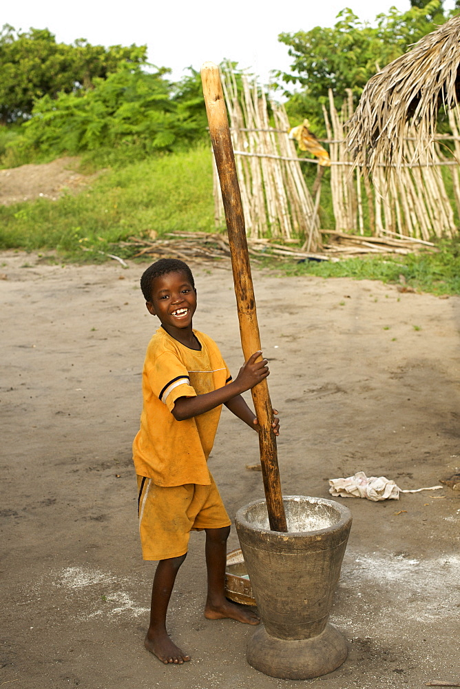 Young boy crushing maize in Guludo village in the Quirimbas National Park in northern Mozambique, Africa