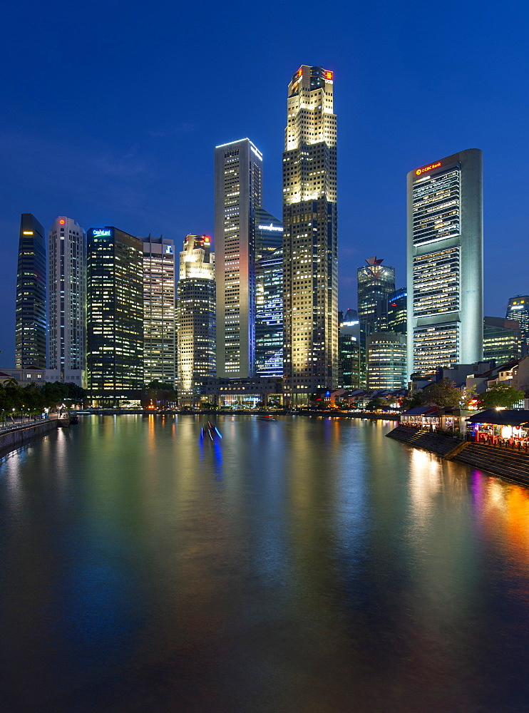 Boat Quay and the Singapore skyline and river at dusk.