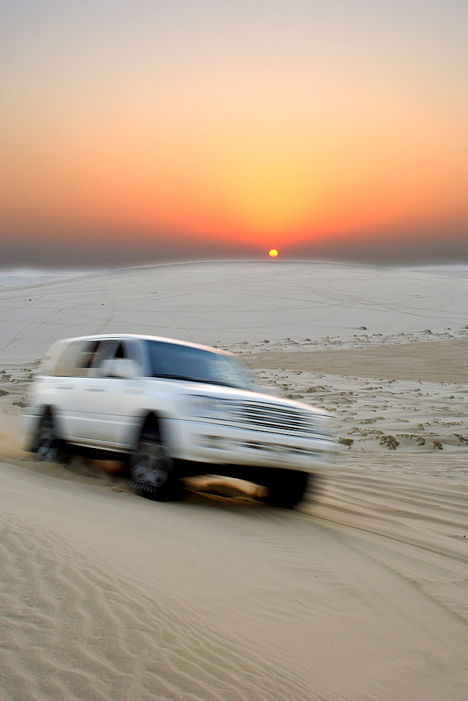 A 4X4 at the Inland Sea (Khor al Adaid) in southern Qatar at sunset.