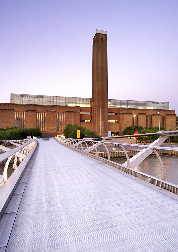 Dawn view of the Tate Modern art Gallery taken from the Millenium bridge in London. The Tate Modern is the converted former Bankside power station on the south bank of the Thames River. It was built in two phases between 1947 and 1963 and was designed by Sir Giles Gilbert Scott.