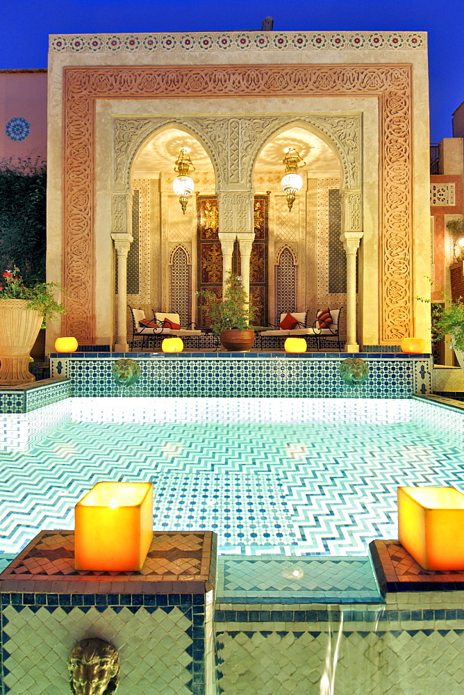 Dusk view of the pool and relaxation area in the Palais Sebban riad in Marrakech, Morocco