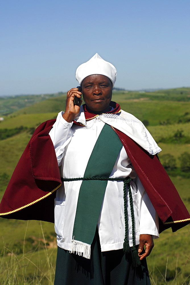 A Xhosa woman talks on her mobile/cell phone in the Eastern Cape Province of South Africa. This is an area along the Coffee Bay road in a region formerly known as the Transkei.