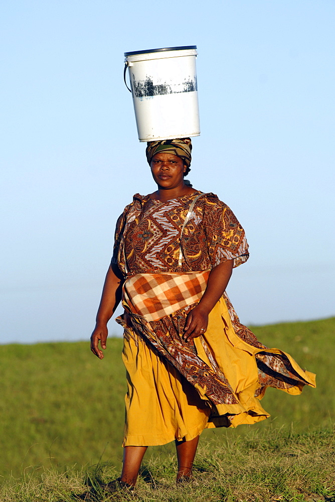 A Xhosa woman walking with a bucket of water on her head, as is traditional in the Eastern Cape Province of South Africa.