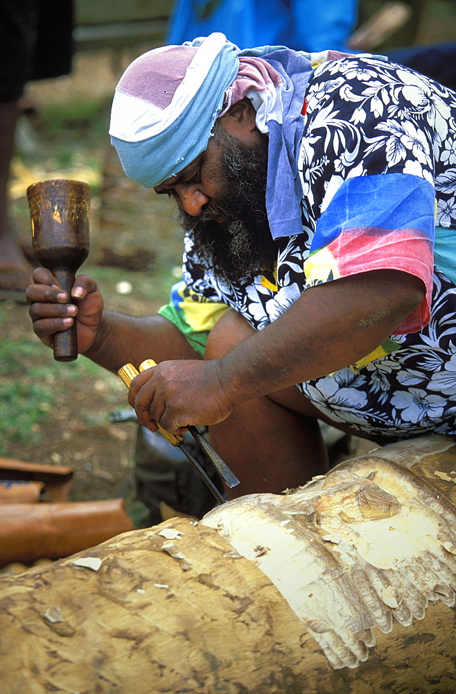 Man carving a statue from a tree trunk at a Melanesian cultural festival in the capital's city centre, Efate Island, Port Vila, Vanuatu