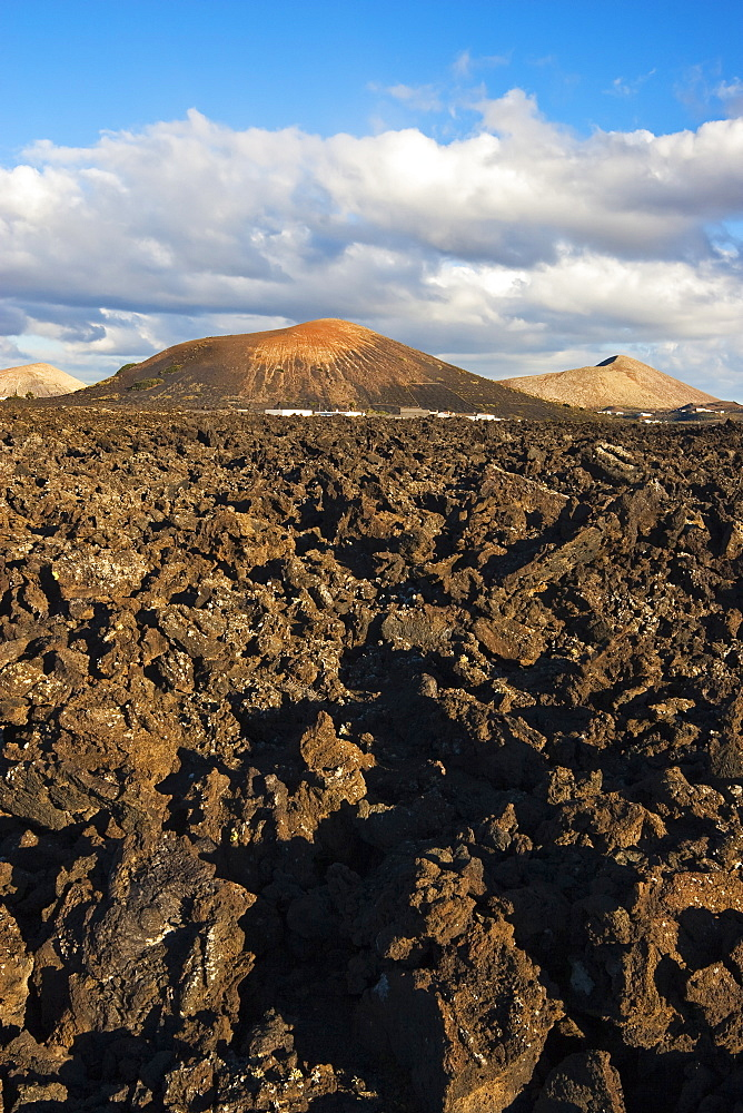 Irregular blocky lava (a'a) and cinder cones of the volcanic landscape of Timanfaya National Park, Lanzarote, Canary Islands, Spain, Atlantic Ocean, Europe