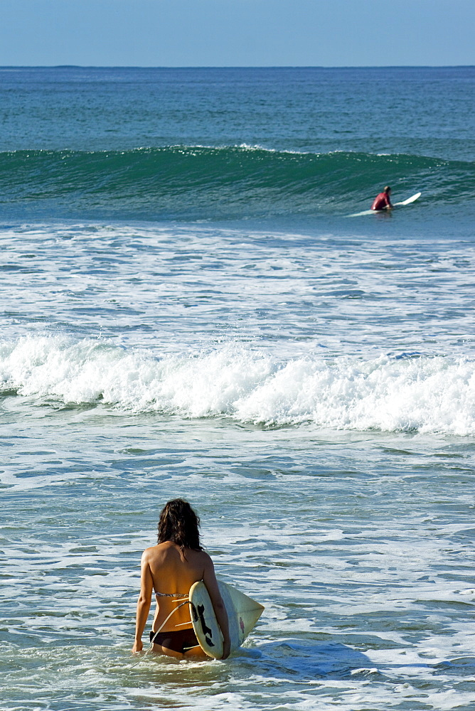 Surfer girl on Playa Guiones beach, Nosara, Nicoya Peninsula, Guanacaste Province, Costa Rica, Central America