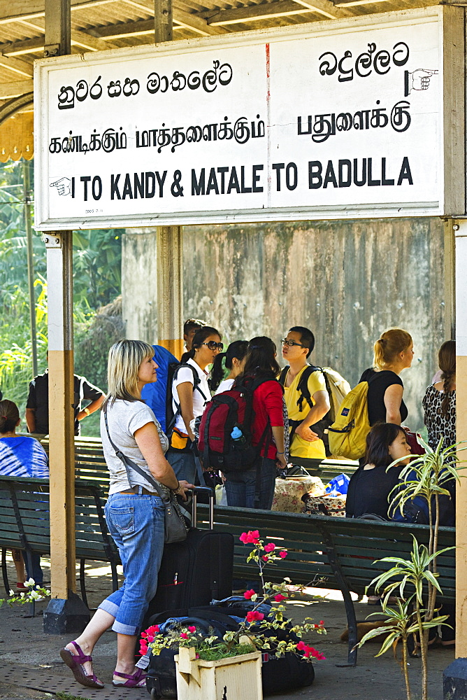 Foreign travellers await the popular Colombo to Badulla train at the railway station at Peradeniya, near Kandy, Sri Lanka, Asia