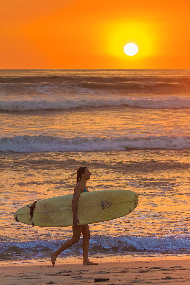 Girl with surfboard at sunset on Playa Guiones surf beach, Nosara, Nicoya Peninsula, Guanacaste Province, Costa Rica, Central America
