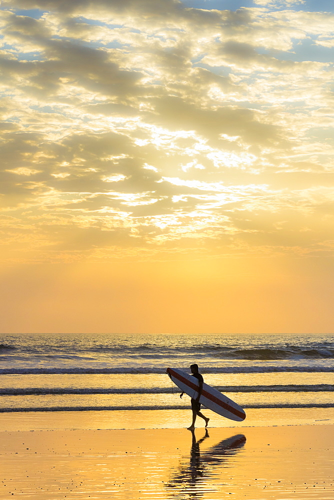 Surfer with long board at sunset on popular Playa Guiones surf beach, Nosara, Nicoya Peninsula, Guanacaste Province, Costa Rica, Central America