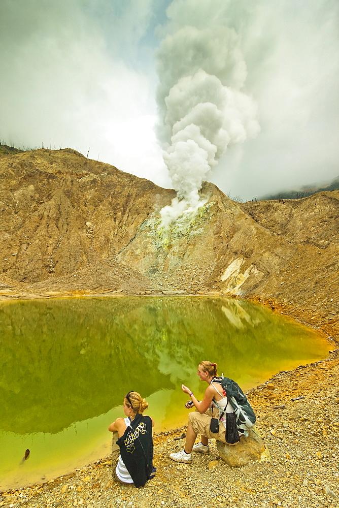 Tourists by green crater lake and fumaroles at Papandayan Volcano, an active four crater caldera, Garut, West Java, Java, Indonesia, Southeast Asia, Asia