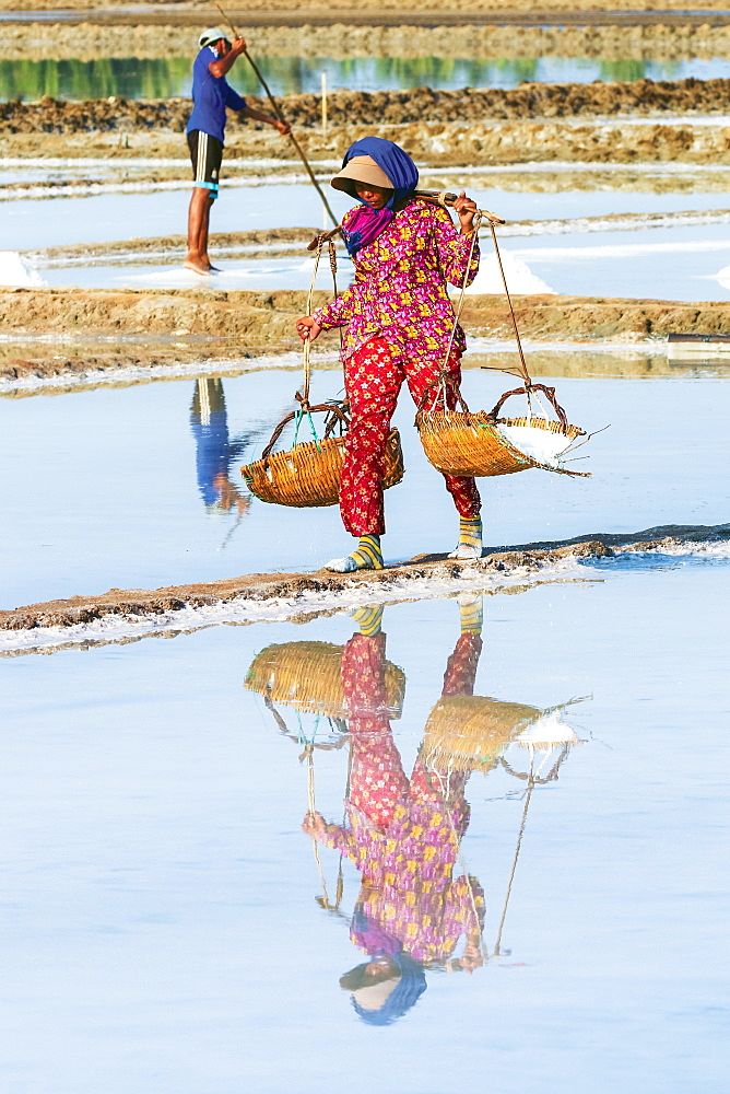 Woman with shoulder pole harvesting the salt fields around the Praek Tuek Chhu River estuary south of the city, Kampot, Cambodia