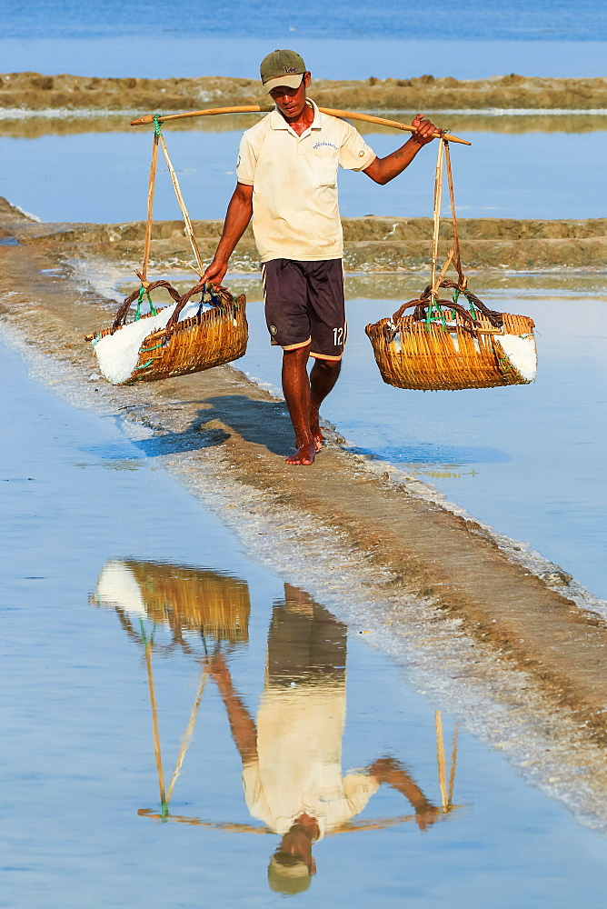 Man with shoulder pole harvesting the salt fields around the Praek Tuek Chhu River estuary south of the city, Kampot, Cambodia, Indochina, Southeast Asia, Asia