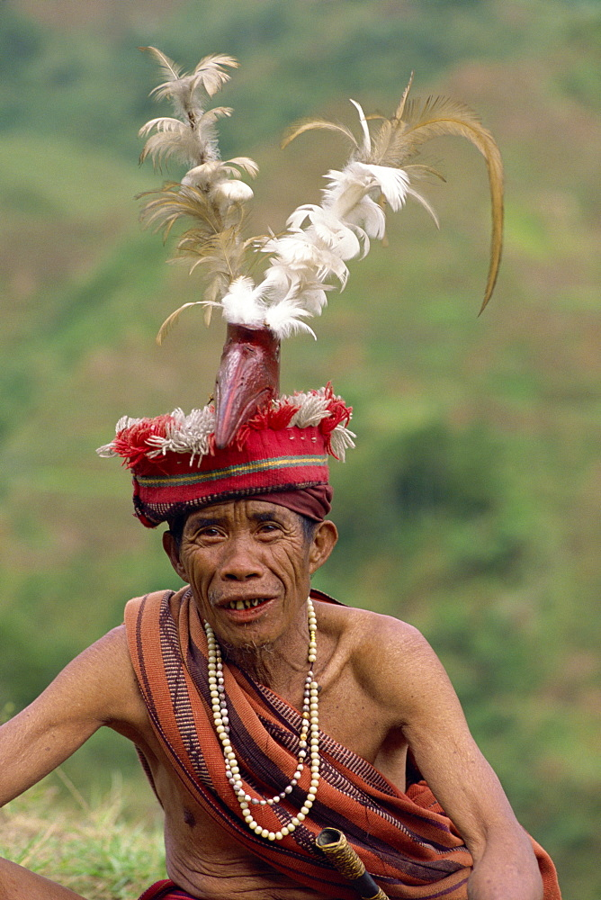 Portrait of an elderly man of the Ifugao tribe wearing a woven hat decorated with feathers and carved bird at Banaue, Mountain Province, north Luzon, Philippines, Southeast Asia, Asia
