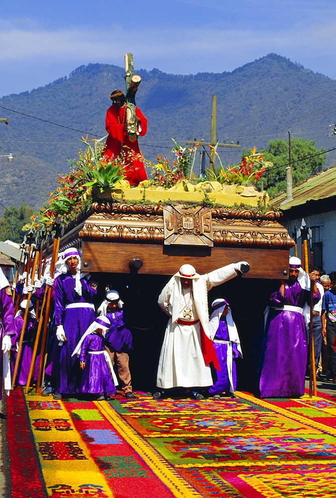 Men carry a huge wooden float of Christ over coloured sawdust carpet during the Easter procession in Antigua, Guatemala, Central America