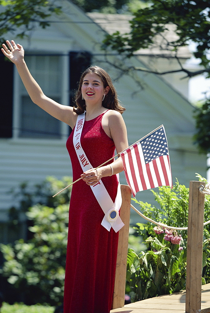 Fourth of July beauty queen with Stars and Stripes flag, waving to parade, Rhode Island, New England, United States of America, North America