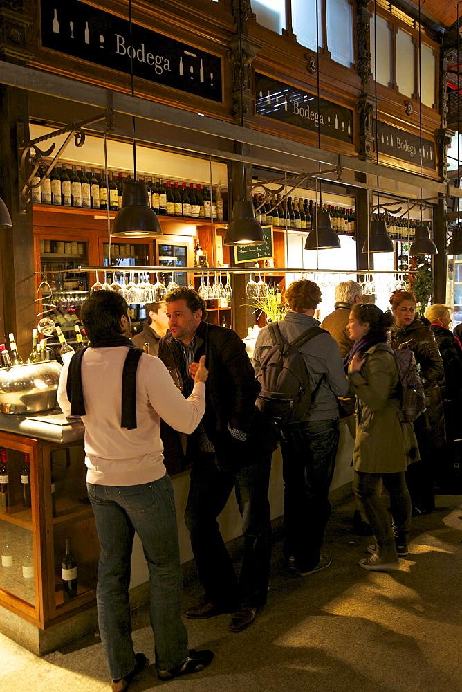 Spanish enjoy tapas and wine in indoor market, Mercado de San Miquel, Madrid, Spain, Europe