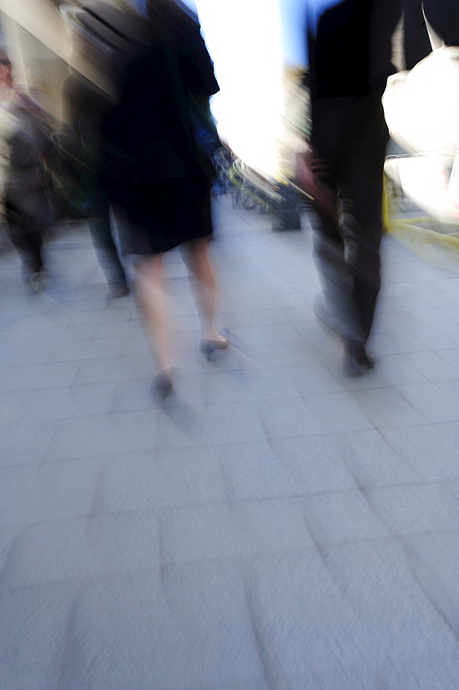 Man and woman in business clothing walking on a sidewalk, motion blur