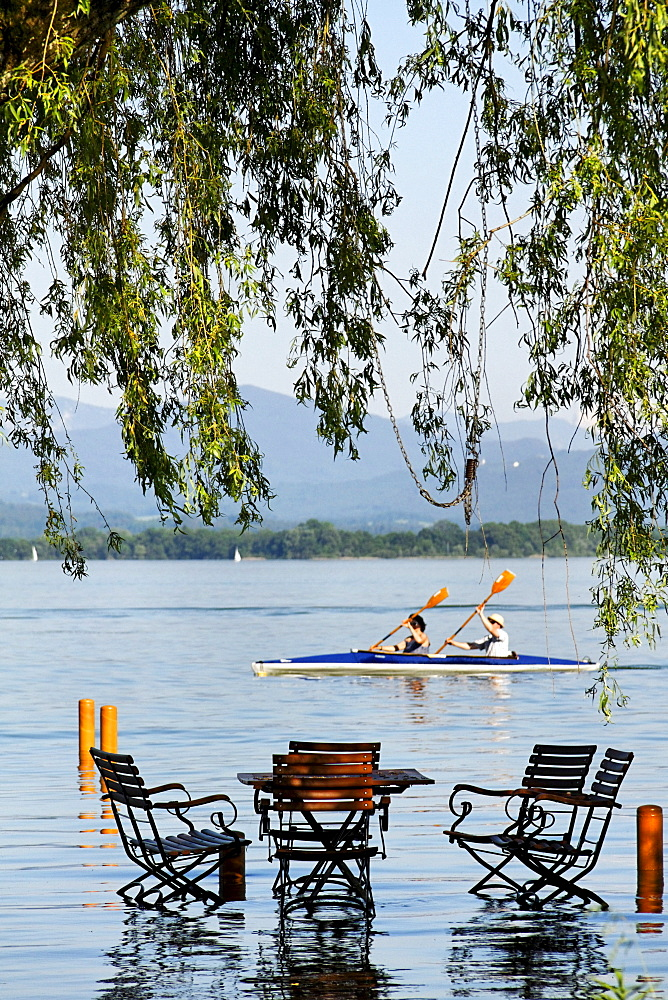 Canoe passing a partly submerged outdoor table setting in lake Chiemsee, Fraueninsel island, Chiemgau, Upper Bavaria, Germany, Europe