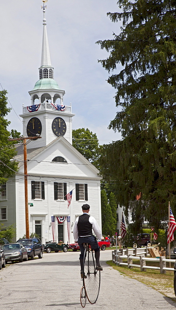 A man rides an antique high wheel bicycle near the Congregational Church of Amherst following the town's July 4 parade, Amherst, New Hampshire, USA