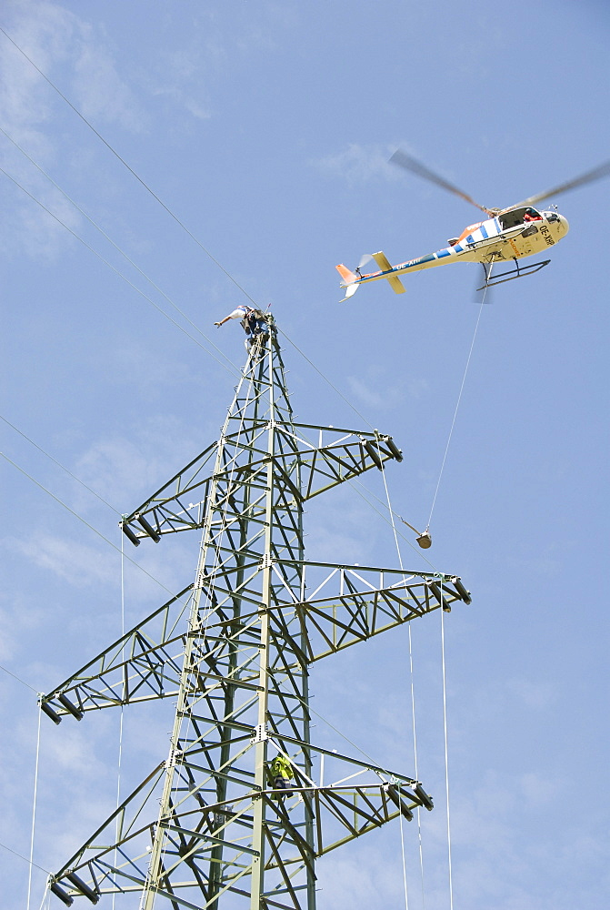 Helicopter connecting power lines, worker on an electricity pylon reaching for the cable, Waldviertel, Forest Quarter, Austria, Europe
