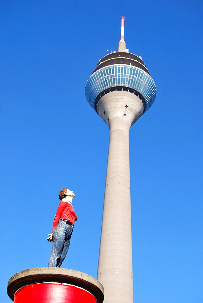 Woman looking up, sculpture on a red pillar pedestal with Rheinturm tower at back, Duesseldorf, North Rhine-Westphalia, Germany, Europe