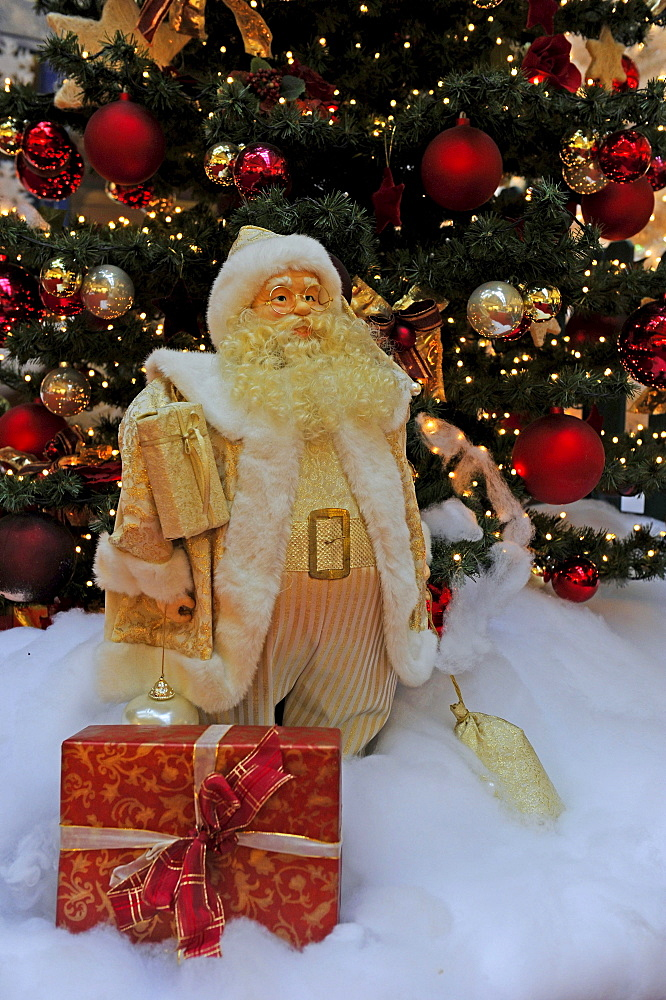 Christmas decoration, Santa Claus with gifts in front of a Christmas tree
