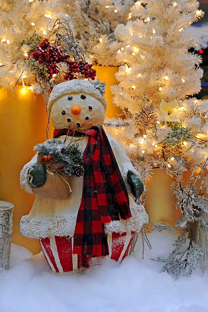 Christmas decorations, snowman in front of a Christmas tree