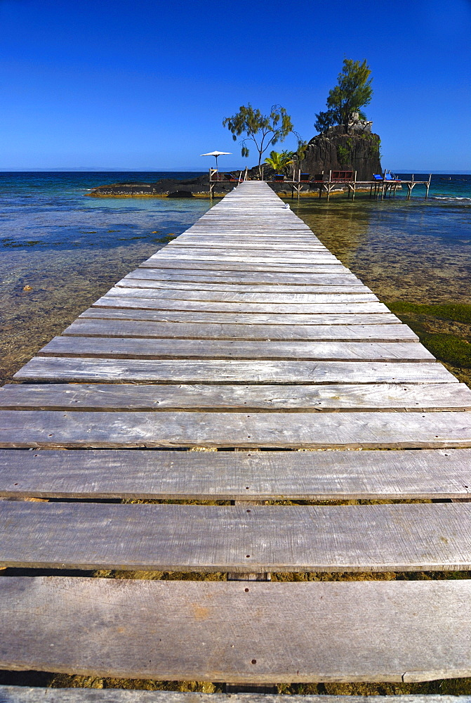 Jetty leading to a small rocky island with sunbeds, Santa Maria island, Madagascar, Africa