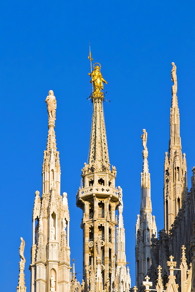 Madonnina statue on cathedral spire against blue sky, Milan city, Italy, Europe