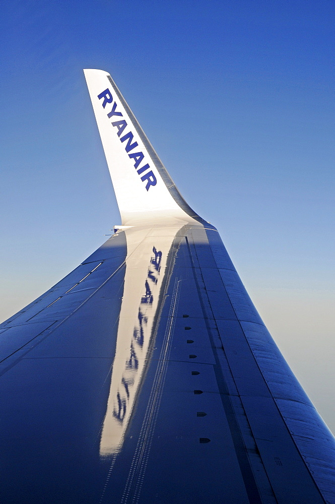 Ryanair, budget airline logo on the wing of a plane in the sky