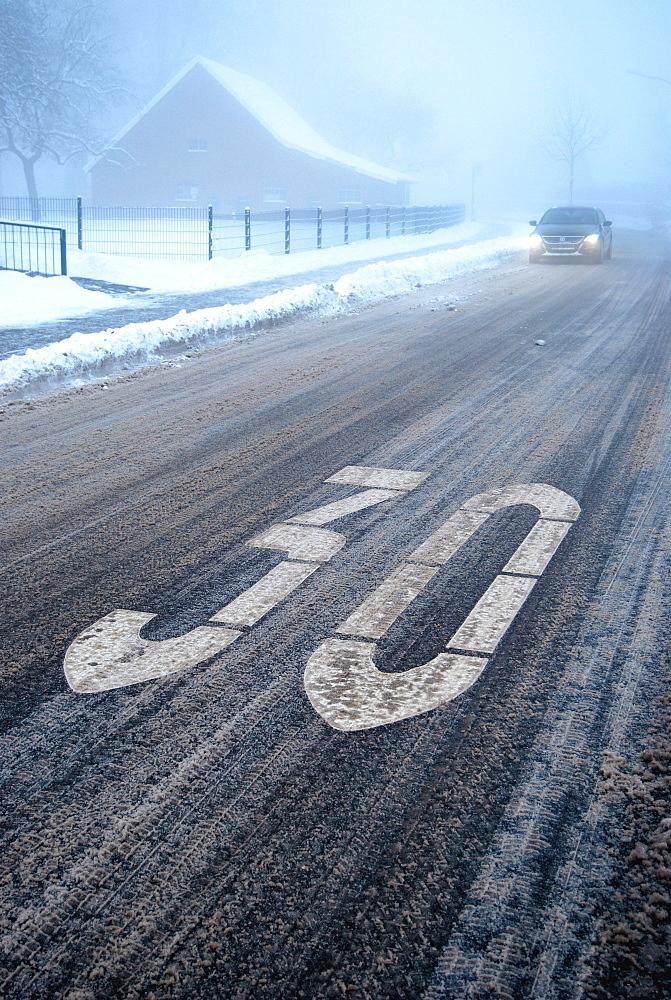 Slip hazard in a traffic calmed area, snow slush on a wintery road with fog, Borken, Gemen district, Muensterland, North Rhine-Westphalia, Germany, Europe