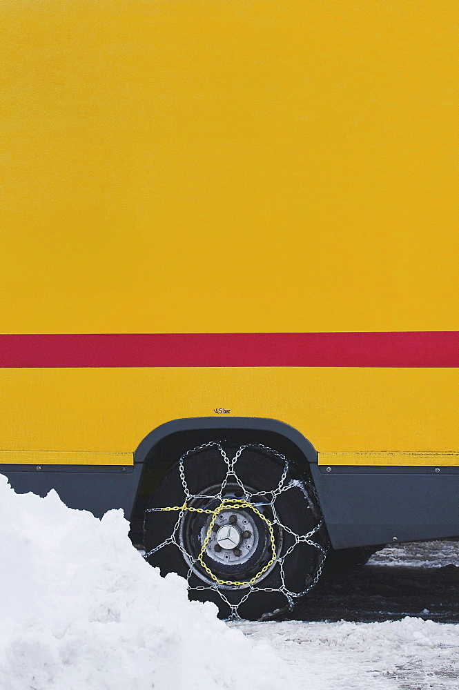 Van with mounted snow chains on a wintry road