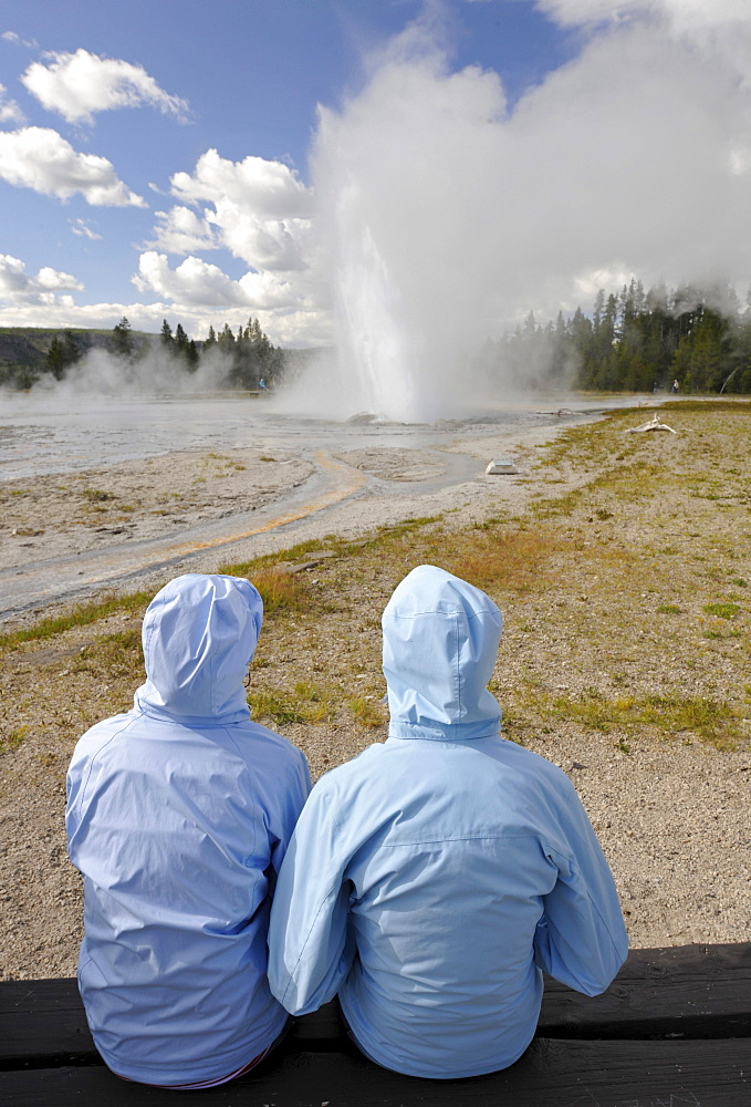 Tourists watching the eruption of the Daisy Geyser, Upper Geyser Basin, geothermal springs in Yellowstone National Park, Wyoming, United States of America, USA