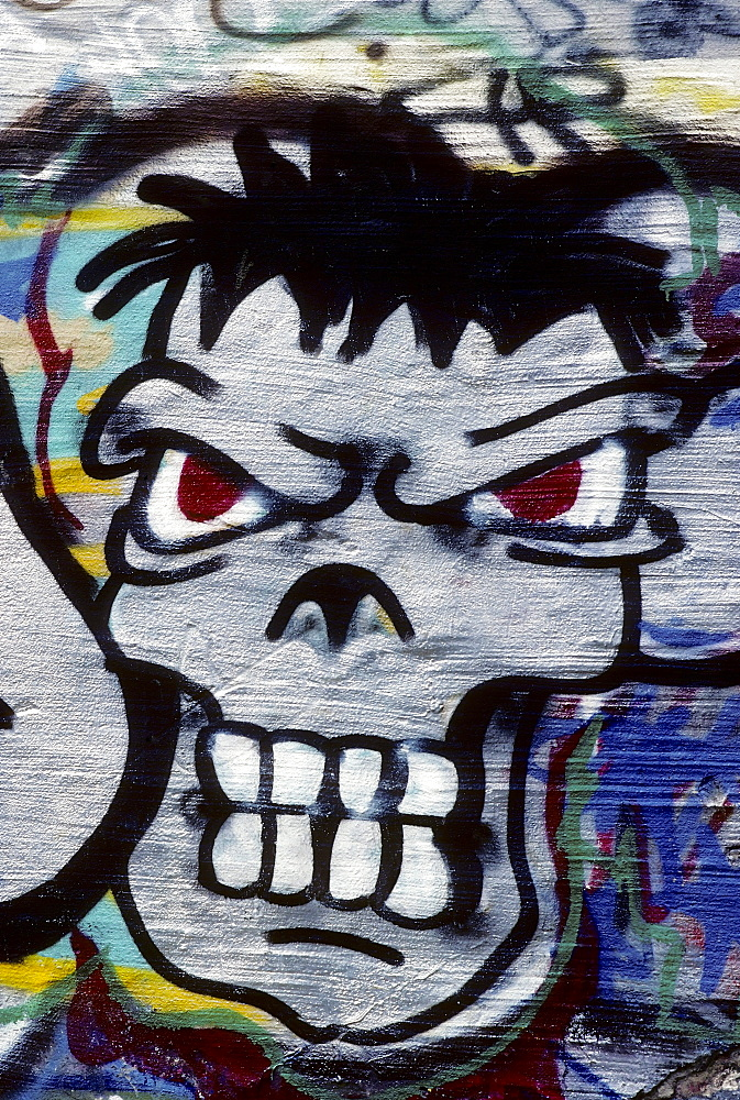 Grim face, looking aggressive with bared teeth, graffiti