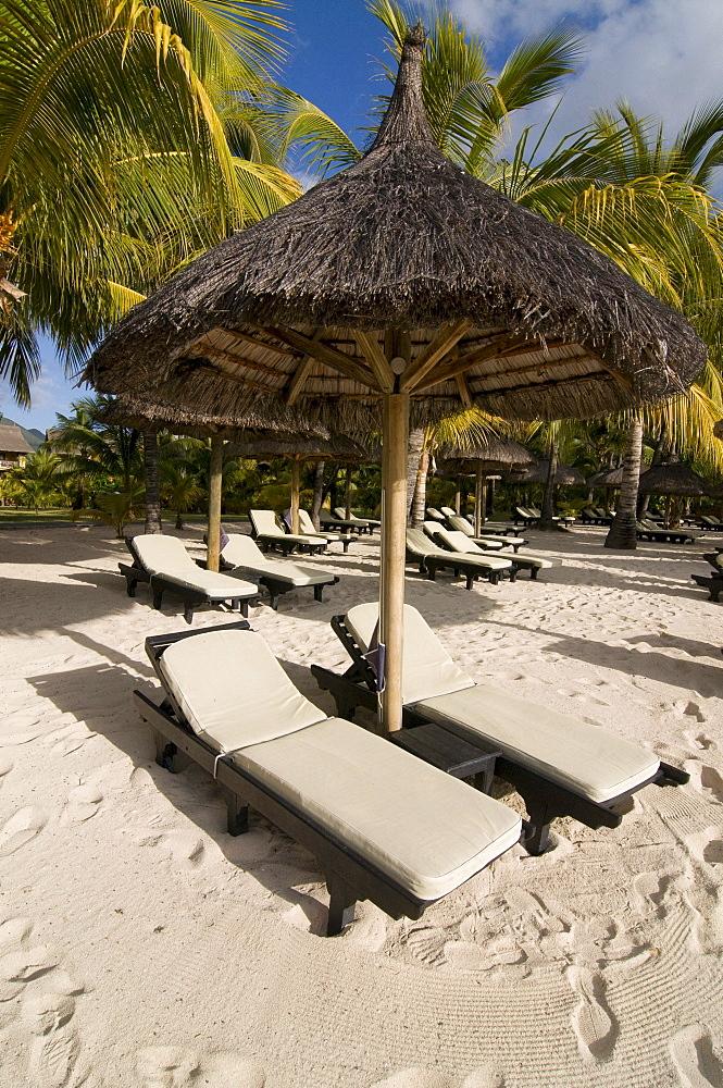 Sunbeds under sunshade on the beach of Le Paradis Hotel, Mauritius, Africa