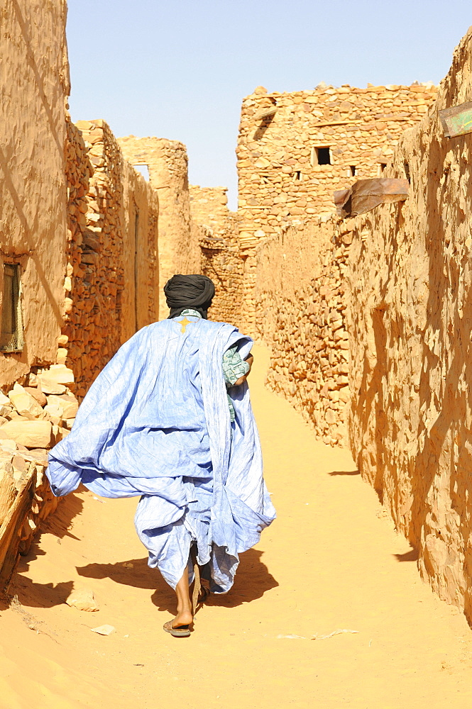 Man walking through the sandy lanes of the town of Chinguetti, Mauritania, northwestern Africa