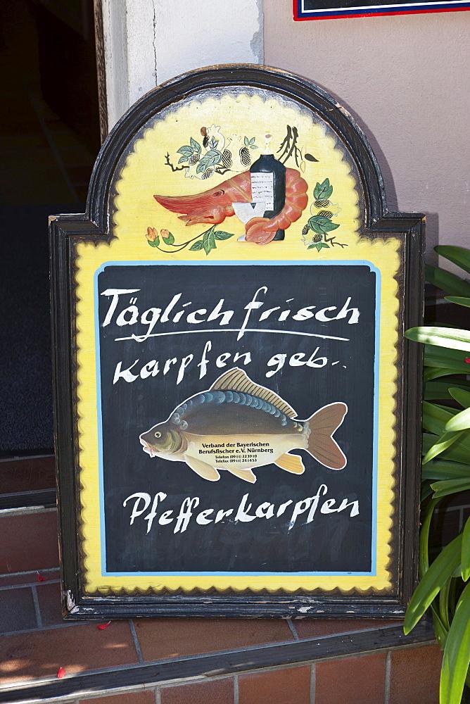 Menu board offering fresh carp, Germany