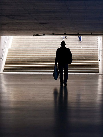 Man carrying a shopping bag in a pedestrian underpass