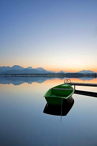 Evening mood at Lake Hopfensee with a boat and a dock near Fuessen, Allgaeu, Bavaria, Germany, Europal