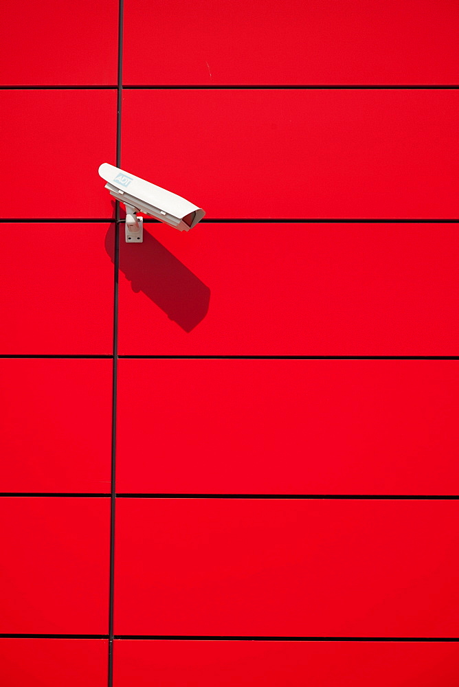 Surveillance camera on a red wall.