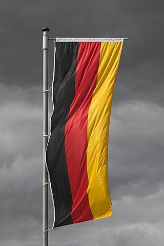 Germany flag hanging vertically in front of a gray cloudy sky