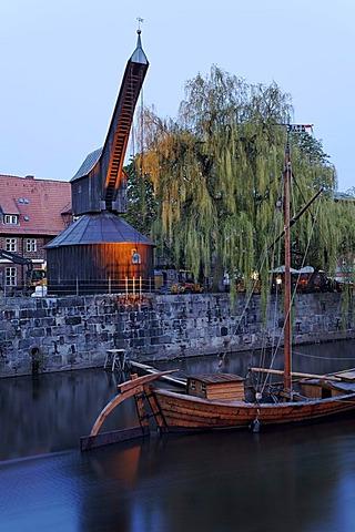Old crane and replica of a salt ship on the Illmenau river, evening mood, historical salt port, Lueneburg, Lower Saxony, Germany, Europe