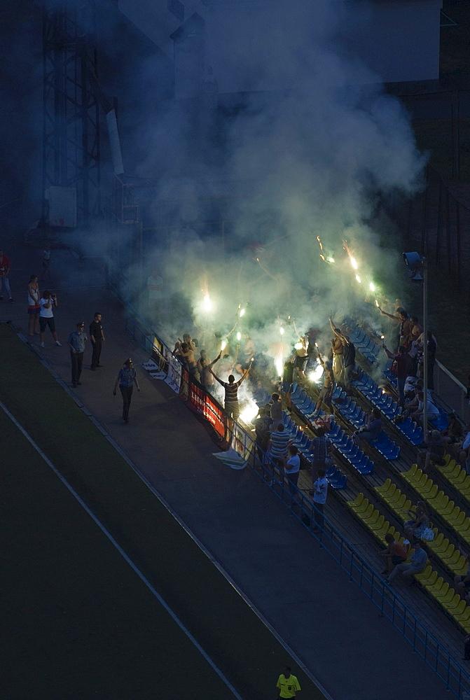 Football fans on tribune lighting fireworks