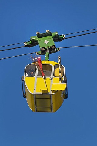 Yellow cabin of the Kampenwandbahn ropeway, with skis on the outside of the cabin and a witch's broom for carnival, Chiemgau, Bavaria, Germany, Europe