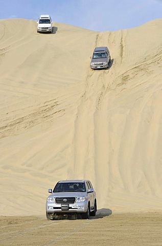 Three off-roaders driving in sand dunes, Emirate of Qatar, Persian Gulf, Middle East, Asia