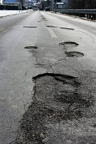 Potholes in an asphalt road caused by frost damage in the cold winter 2009-2010