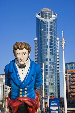Figurehead from the former HMS Vernon ship at canalside of Gunwharf Quays with The Number One Tower, Lipstick, at back, Portsmouth, Hampshire, England, United Kingdom, Europe